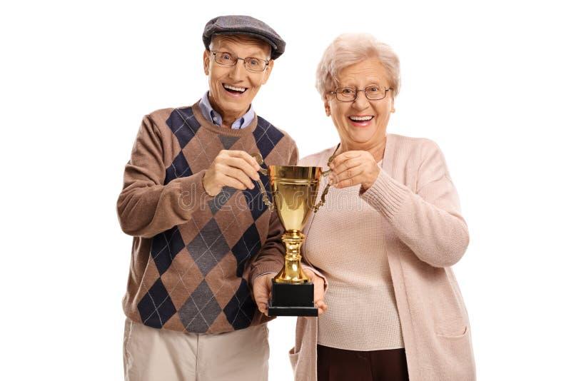 Bejaarde en bejaarde die een gouden trofee houden stock fotografie
