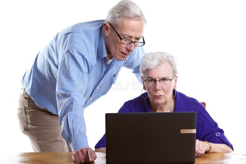 Bejaarde en vrouw achter laptop stock foto