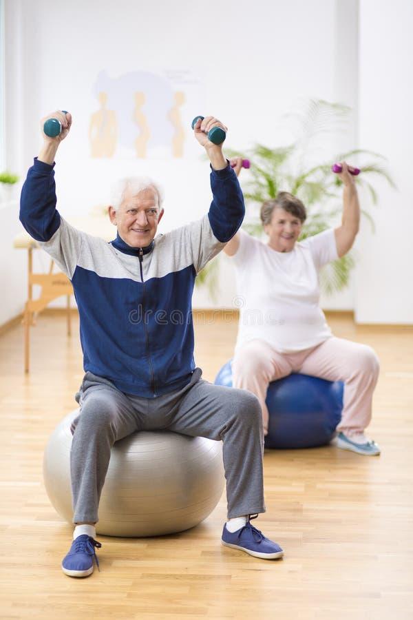 Bejaarde en vrouw die op gymnastiek- ballen tijdens fysiotherapiezitting bij het ziekenhuis uitoefenen stock foto's