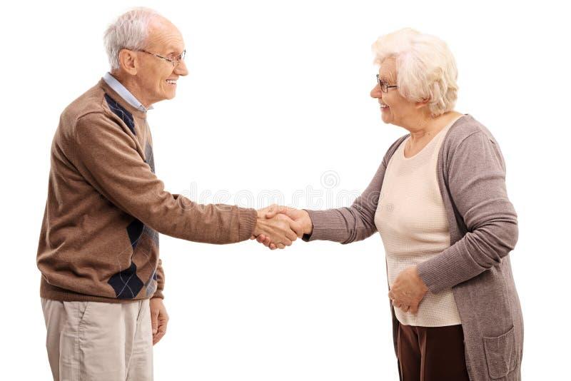 Bejaarde en vrouwen het schudden handen stock foto's