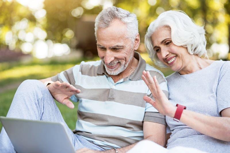 Bejaarde familie die Internet voor communicatie zitting in een park gebruiken royalty-vrije stock fotografie