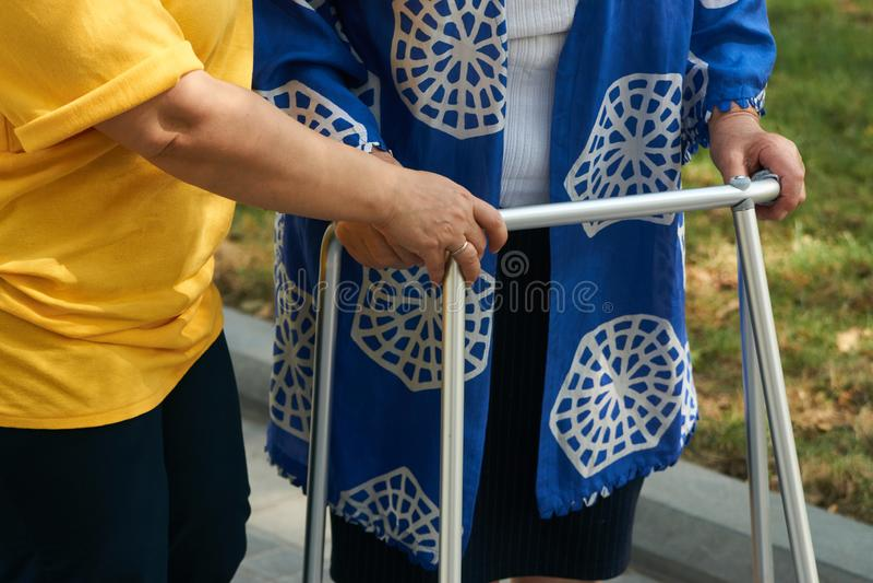 Bejaarde fysieke therapie door verzorger in het ziekenhuisbinnenplaats, close-up stock afbeeldingen