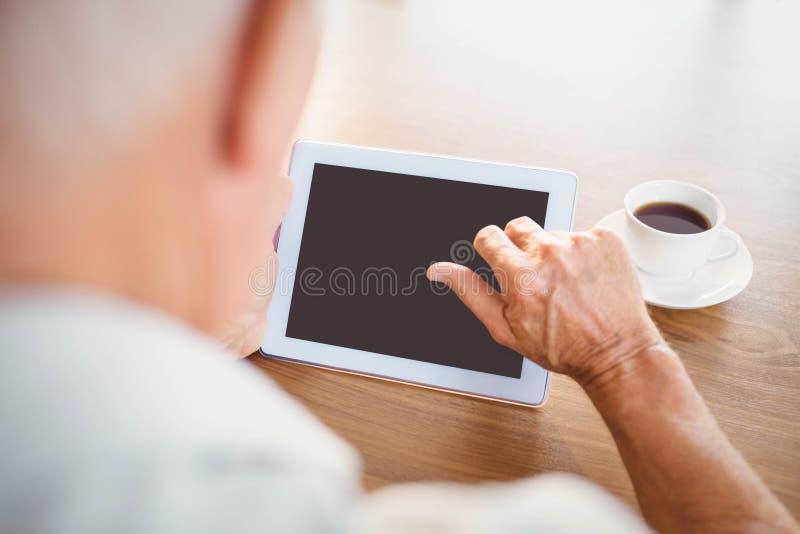 Bejaarde gebruikend tablet en drinkend koffie stock afbeelding