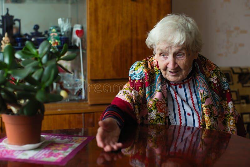Bejaarde gelukkige vrouw die in heldere klerengebaren bij de lijst zitten royalty-vrije stock foto's