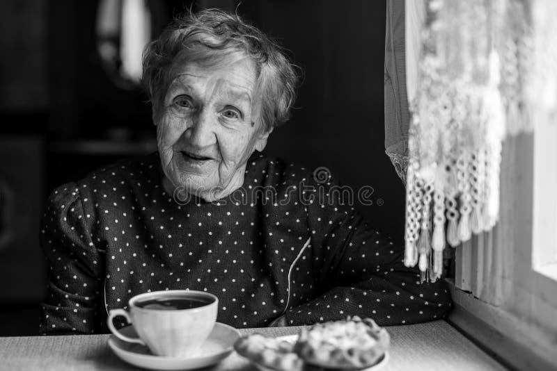 Bejaarde gelukkige vrouw het drinken thee binnen bij zijn huis royalty-vrije stock foto