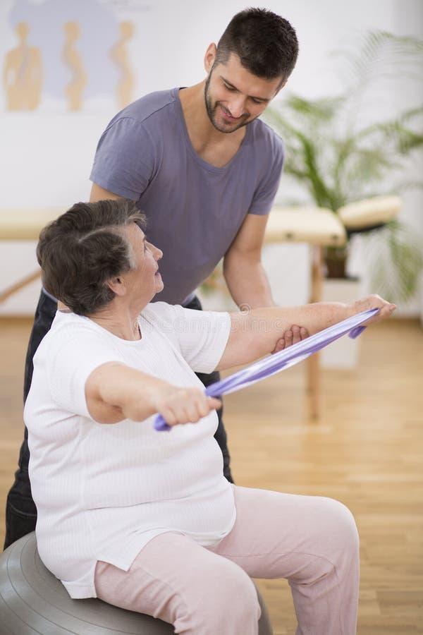Bejaarde gepensioneerde die met weerstandsbanden uitoefenen met haar professionele fysiotherapeut royalty-vrije stock foto