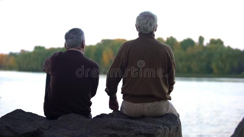 Bejaarde gepensioneerden die bos en water van zitting op rivierbank genieten, weekendrust royalty-vrije stock foto