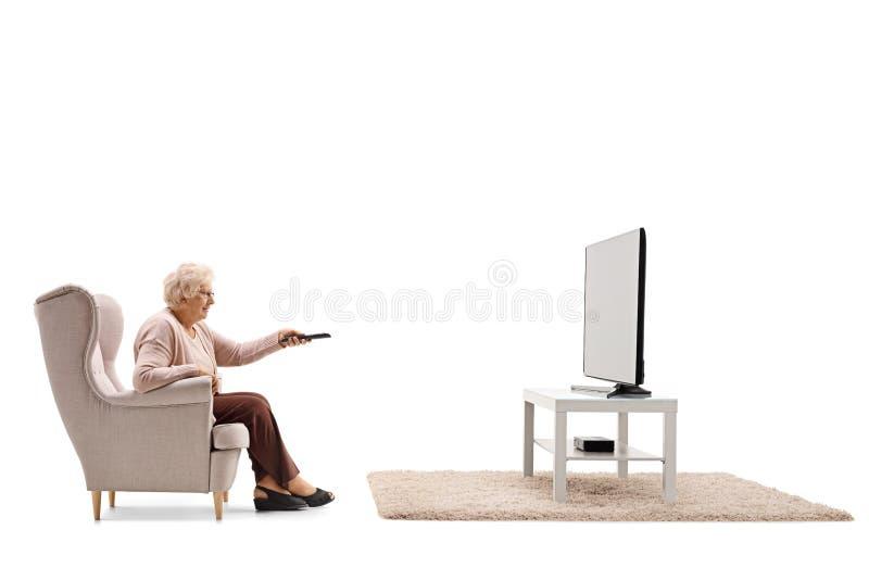 Bejaarde gezet in een leunstoel het letten op televisie royalty-vrije stock foto