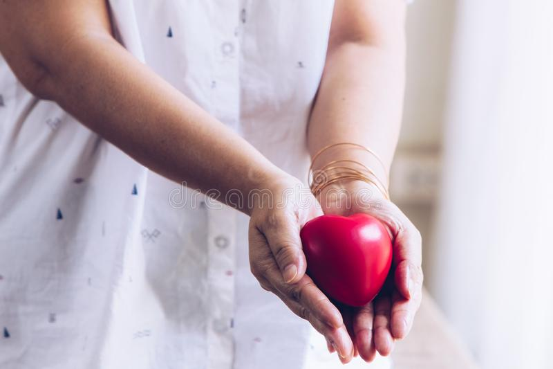 Bejaarde hand met wond die rood hart dragen Aziatisch bejaarde die rode hartvorm houden stock afbeelding