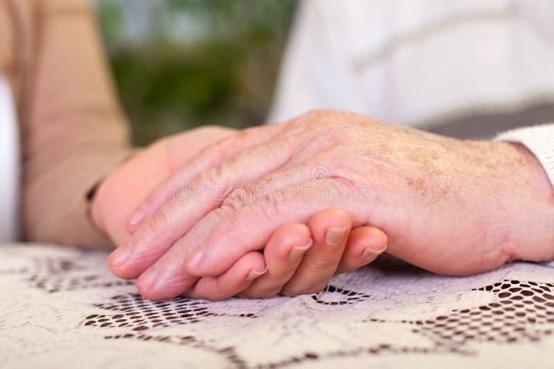 Bejaarde handen die werker uit de hulpverlening` s handen houden stock afbeeldingen