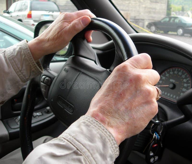 Bejaarde handen op stuurwiel royalty-vrije stock afbeelding