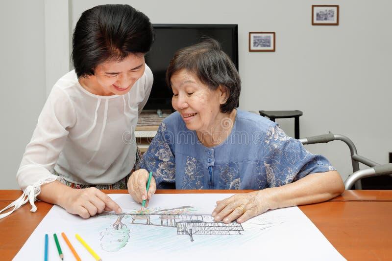 Bejaarde het schilderen kleur met dochter stock fotografie