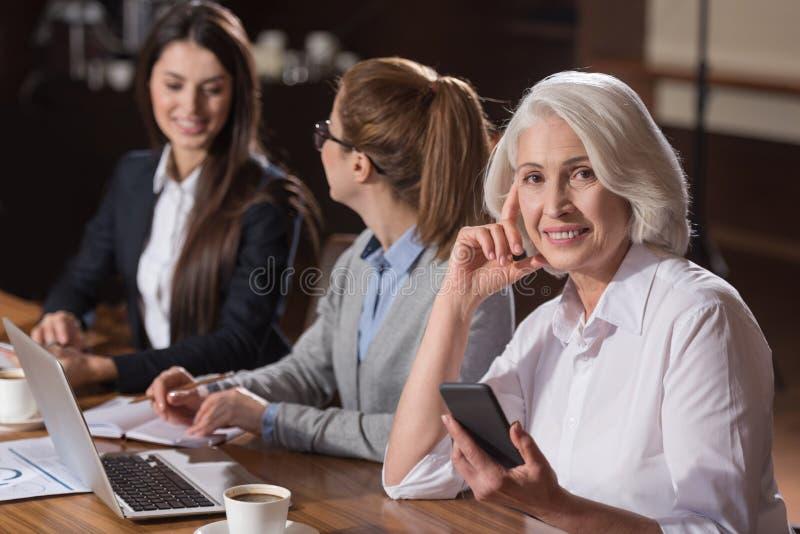Bejaarde het stellen met haar jonge collega's stock foto