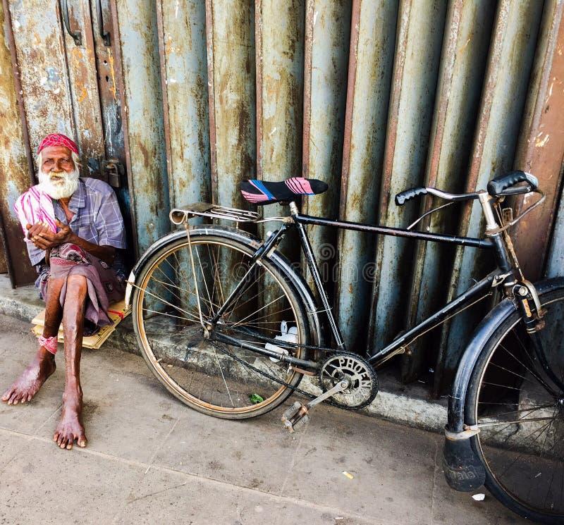 Bejaarde Hindoese fietser die op de straat met zijn fiets rusten stock afbeeldingen