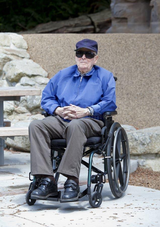 Bejaarde hogere mens in rolstoel buiten stock afbeelding