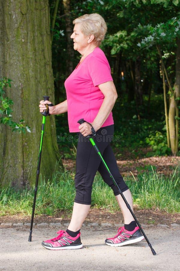 Bejaarde hogere vrouw die het noordse lopen, sportieve levensstijlen in oude dag uitoefenen stock afbeelding