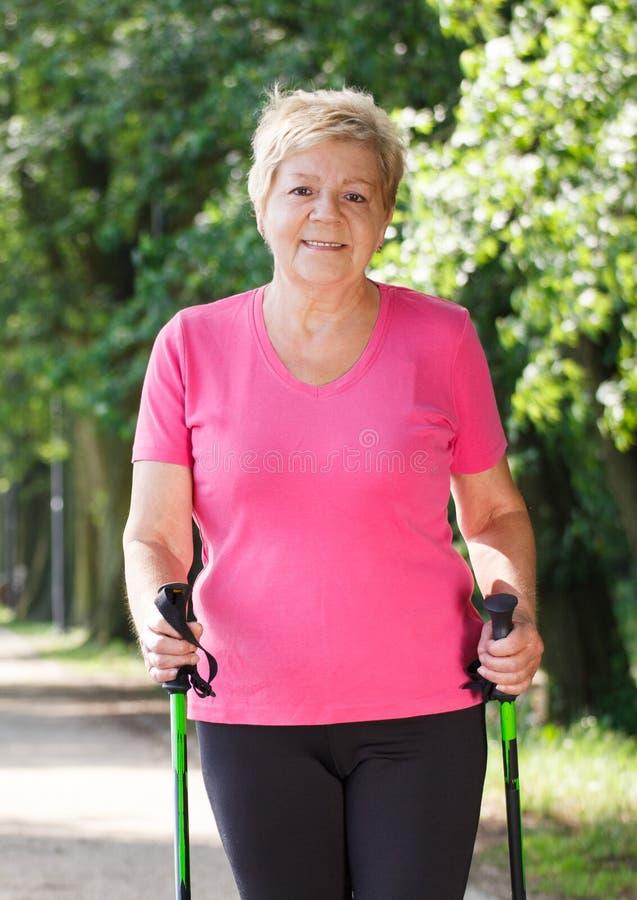 Bejaarde hogere vrouw die het noordse lopen, sportieve levensstijlen in oude dag uitoefenen stock afbeeldingen