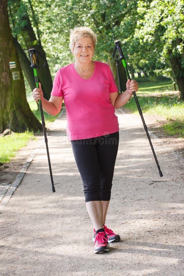 Bejaarde hogere vrouw die het noordse lopen, sportieve levensstijlen in oude dag uitoefenen stock fotografie