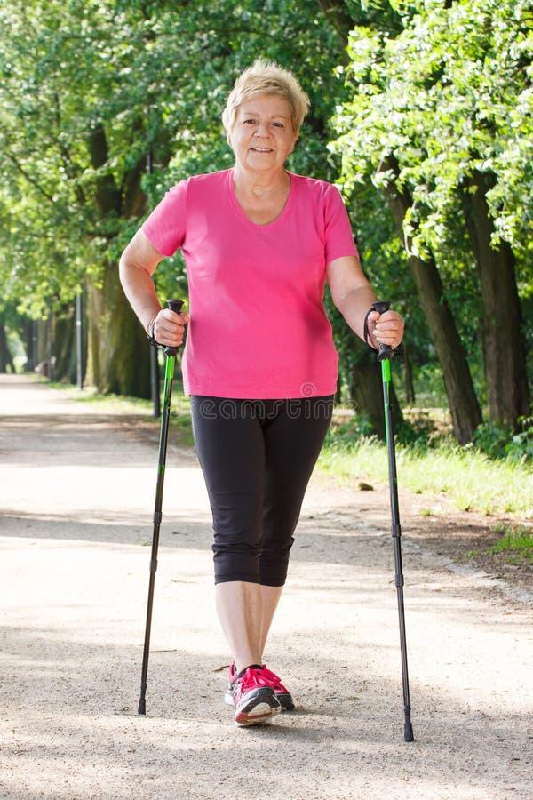 Bejaarde hogere vrouw die het noordse lopen, sportieve levensstijlen in oude dag uitoefenen royalty-vrije stock foto's