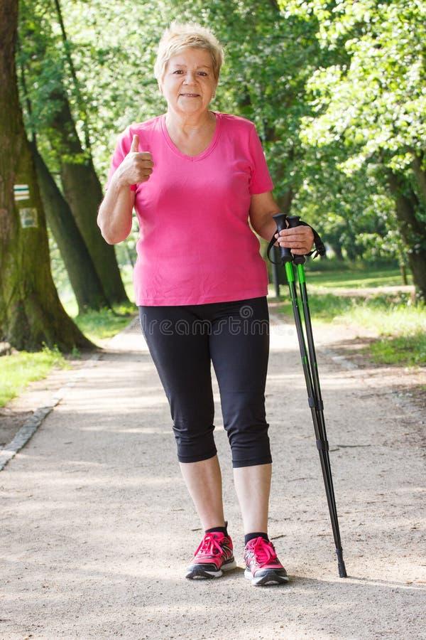 Bejaarde hogere vrouw die het noordse naar boven gaan uitoefenen en duimen tonen, sportieve levensstijlen royalty-vrije stock foto