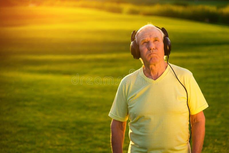 Bejaarde in hoofdtelefoons royalty-vrije stock foto