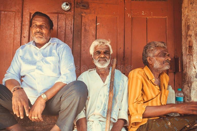 Bejaarde Indische mens drie die openlucht afgelopen houten deur van stadsmarkt zitten royalty-vrije stock afbeelding