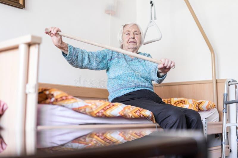 Bejaarde 96 jaar oude vrouwen die met een stokzitting uitoefenen op slecht haar stock afbeeldingen