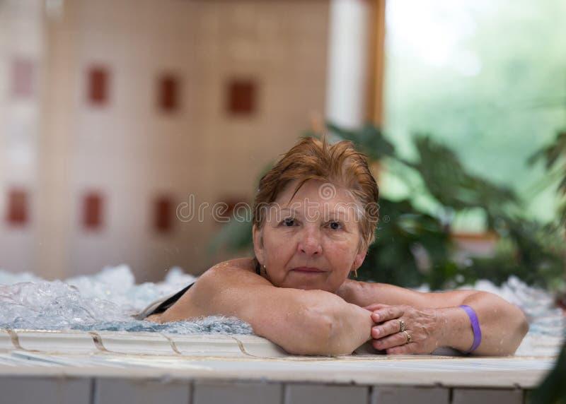 Bejaarde in Jacuzzi stock foto's