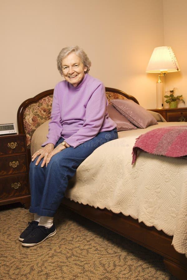 Bejaarde Kaukasische vrouw in slaapkamer. stock fotografie