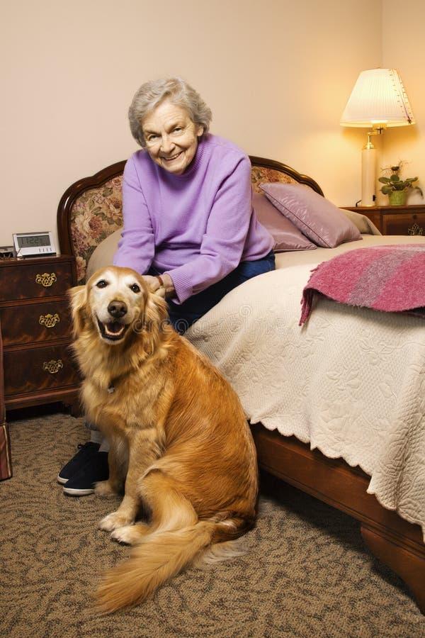 Bejaarde Kaukasische vrouw in slaapkamer met hond. stock foto