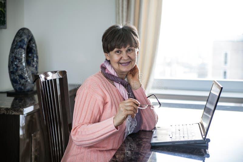 Bejaarde knappe vrouw die aan laptop werken Portret in binnenlands binnenland royalty-vrije stock foto