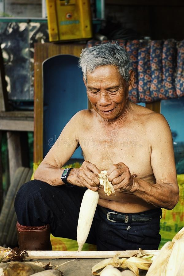 bejaarde landbouwersmens die het graan voor de markt schoonmaken stock afbeelding