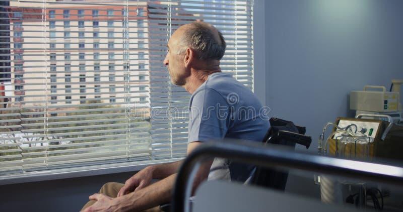 Bejaarde mannelijke pati?nt in het ziekenhuis dichtbij het venster stock foto's