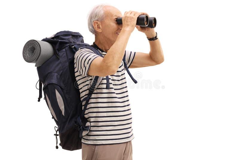 Bejaarde mannelijke wandelaar die door verrekijkers kijken royalty-vrije stock fotografie