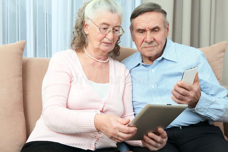 Bejaarde mensen Bejaarde laptop van de paarholding, smartphone en maakt aankopen over Internet in de comfortabele woonkamer van h stock foto