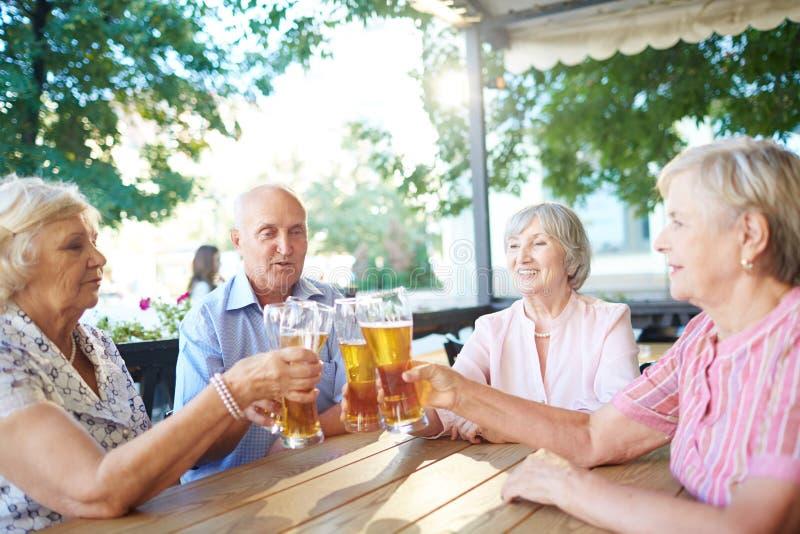 Bejaarde mensen die bierglazen samen klinken stock foto's