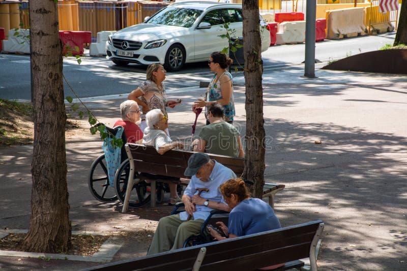 Bejaarde mensen die bij bankslaap het spreken zitten stock foto's