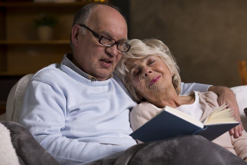 Bejaarde mensen die boek lezen stock foto's