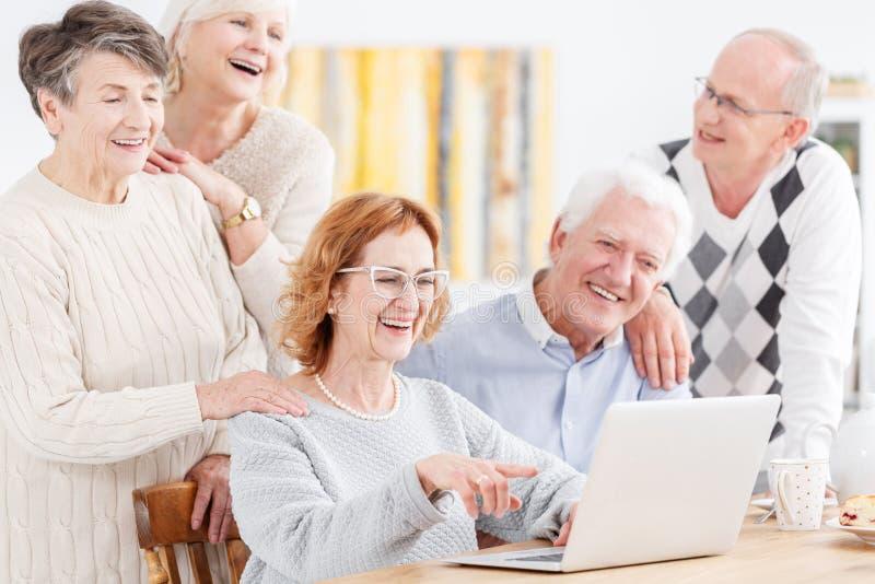 Bejaarde mensen die laptop bekijken stock fotografie