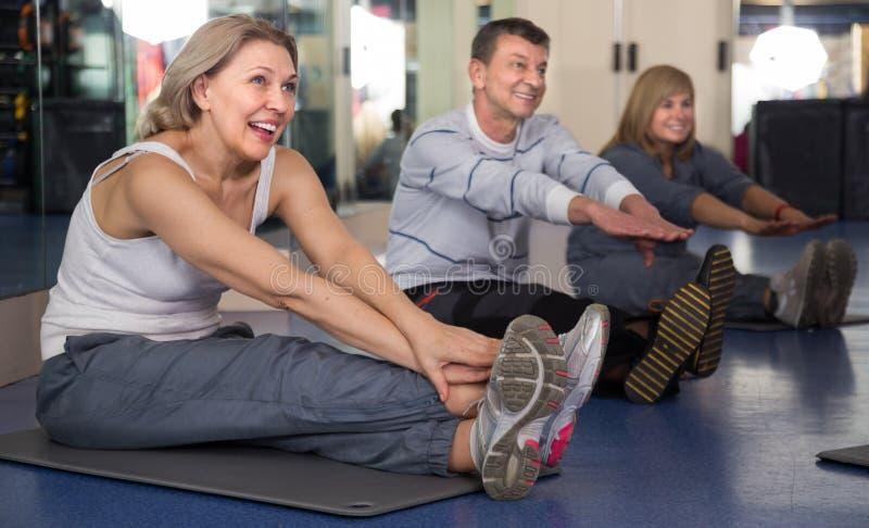 Bejaarde mensen die oefening op mat in moderne gymnastiek doen stock foto's