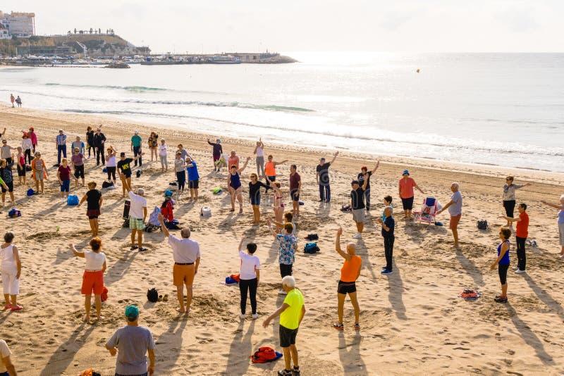 Bejaarde mensen die oefeningen op het strand doen Gezonde levensstijl, actieve levensstijlgepensioneerde in Benidorm, Spanje royalty-vrije stock afbeeldingen