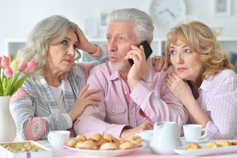 Bejaarde mensen die ontbijt hebben en mobiele telefoon met behulp van stock afbeelding