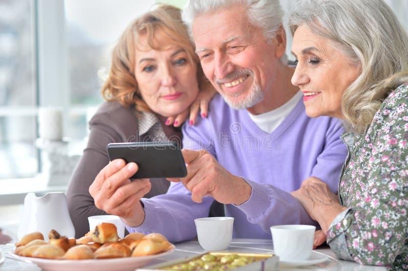 Bejaarde mensen die ontbijt hebben en mobiele telefoon met behulp van royalty-vrije stock afbeeldingen