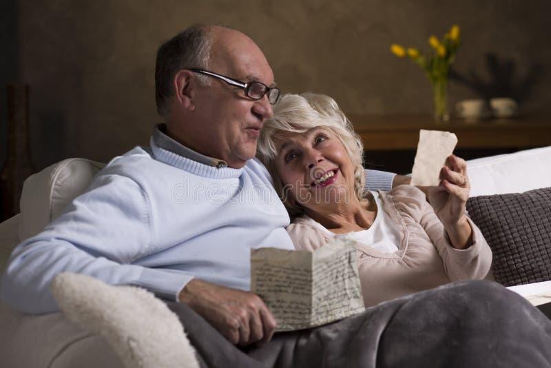 Bejaarde mensen die oude brieven lezen stock afbeelding
