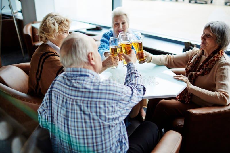 Bejaarde mensen met bierglazen stock foto's