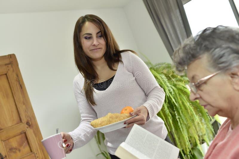 Bejaarde met een dienend ontbijt van de huiswerker uit de hulpverlening stock afbeeldingen