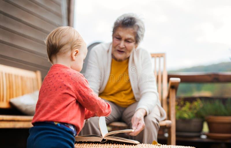 Bejaarde met een peuter groot-kleinkind op een terras in de herfst royalty-vrije stock fotografie