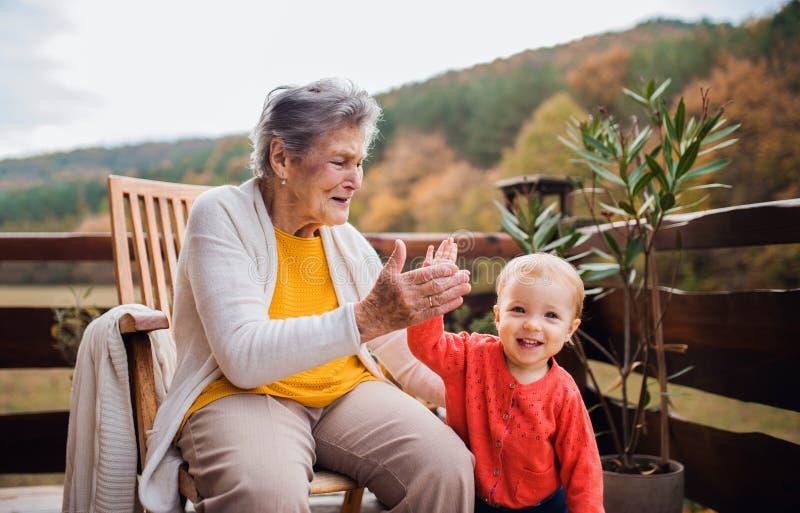 Bejaarde met een peuter groot-kleinkind op een terras in herfst, die hoogte vijf de geven stock afbeeldingen