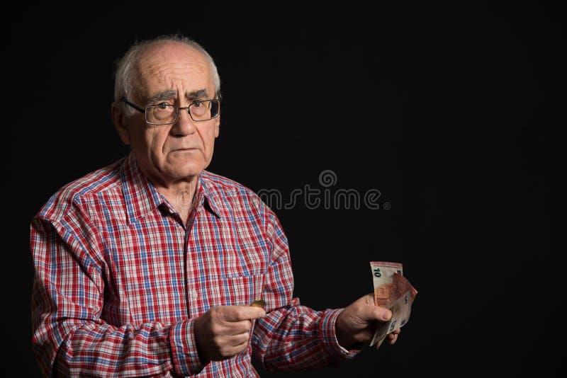 Bejaarde met geld stock foto