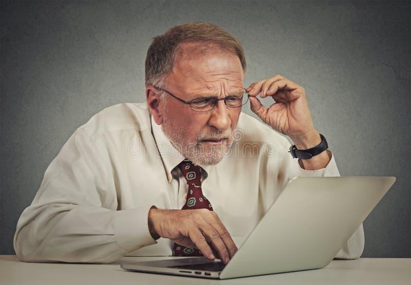 Bejaarde met glazen met laptop software wordt verward die stock foto's